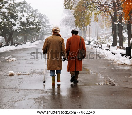 Older man walking at the park in November