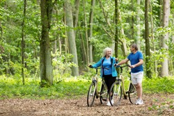 Older marriage standing with bicycles in the forest. Outdoor activities. Retirement.