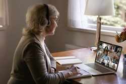 Older mature businesswoman in headphones holding online video call conference brainstorming meeting with diverse colleagues using computer application, distant communication, remote workday concept.