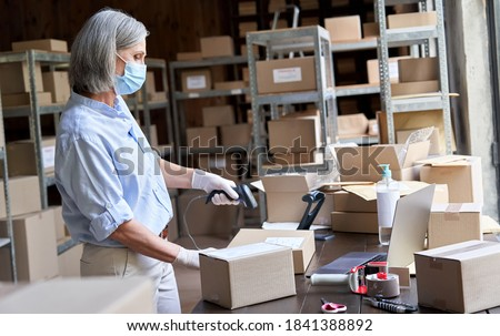 Older mature female online store small business owner worker wearing face mask packing package scanning postal drop shipping ecommerce retail order in box preparing delivery parcel in stock warehouse.