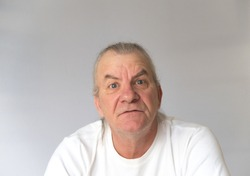 older mature man showing aggression with very angry expression on face. distorted expression. Studio