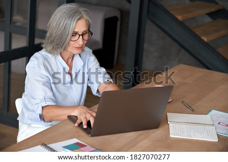 Older mature middle aged business woman employee using laptop typing computer sitting at workplace desk. Senior old lady 60s grey-haired businesswoman entrepreneur or executive working on pc in office