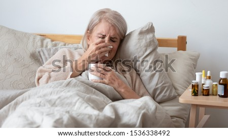 Older mature upset ill woman holding handkerchief blowing running nose in bed at home, sick old senior lady got infectious influenza virus disease flu grippe symptoms sneezing caught cold concept