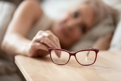 Older mature woman holding taking optical glasses from bedside table waking up in morning, old people eye sight problem, optometry optics ophthalmology, bad vision concept, eyeglasses close up view