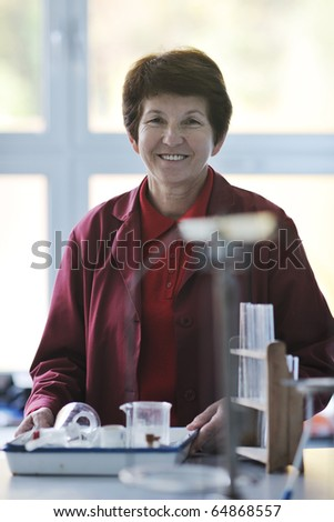 older or senior science and chemistry teacher woman portrait at classroom school indoor