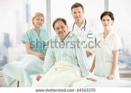 Older patient sitting on bed with hospital crew in background. - stock photo