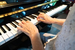 older retired woman practice playing classic piano song during free time