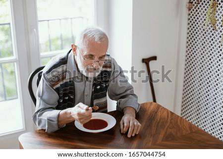 Older sad man eating dinner by himself at home Stockfoto ©