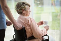 Older sad woman on wheelchair looking through the window
