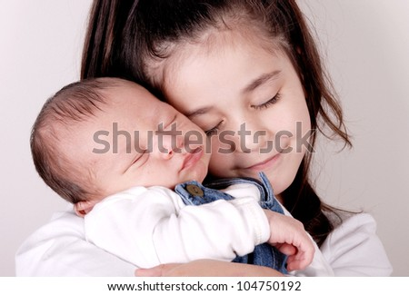 older sister hugging newborn baby brother