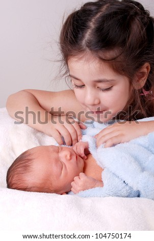 older sister looking at newborn baby brother