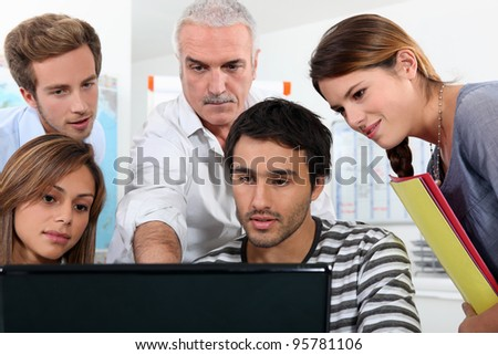 Older students and teacher gathered round a computer