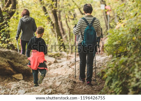 Older woman and two kids are descending on a mountain path in a forest. A group using hiking poles and sport clothes to descend down the hiking path.