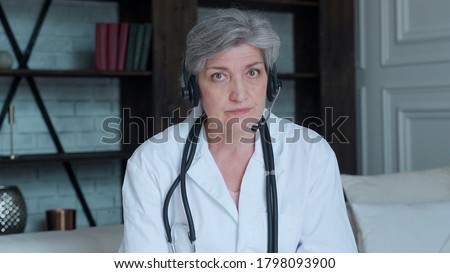 Older woman doctor therapist wearing headset video call talking to web camera consulting virtual patient online by video conference call chat.