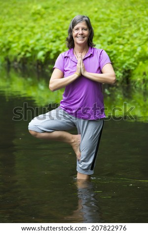 older woman doing yoga in a river