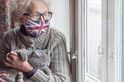 Older woman in a protective mask with a British flag and cat stays at home looking out the window. Lockdown in the UK. Coronavirus mutated covid-19. Strengthening quarantine. Health of the elderly