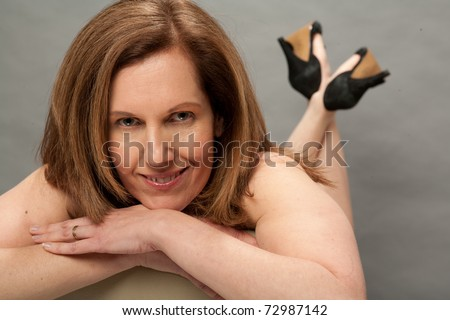 stock photo : Older woman laying on belly looking sexy