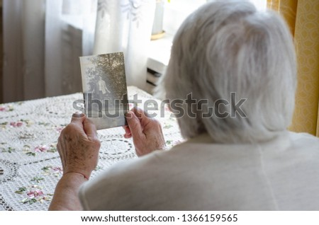 Older woman looking to the photo with young herself. Vintage photos, nostalgie Photo stock ©