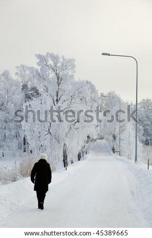 Older woman walking on a snowy road - stock photo