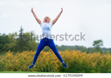 Older woman wearing workout outfit jumping for joy with arms and legs spread in midair in front of blurry yellow flowers #1179190099
