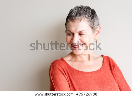 Older woman with short grey hair and orange top smiling #495726988