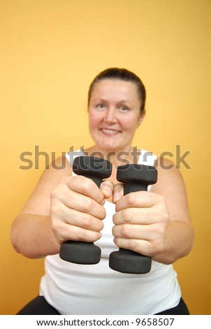 Older woman working out with weights; focus on the hands with weights