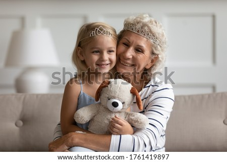 Older younger generations relatives people wear crowns on heads play sitting on couch at home. Loving elderly grandma hugs little princess kid girl hold stuffed bear toy enjoy priceless time together