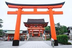 Oldman and Great Torii gate and the Romon Gate at Fushimi Inari taisha shrine, Kyoto, Japan