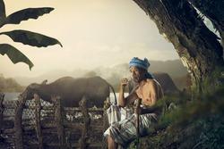 Oldman sit while smoking and watch the buffalo.