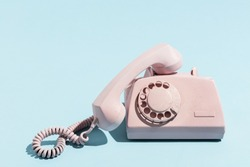 Oldschool pink telephone on a blue background. Telecommunication. Vintage objects.