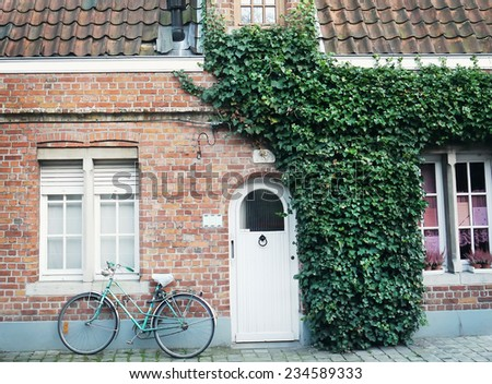 Oldstyle bicycle in front of the red brick wall of a building partilly covered with ivy with a door and windows in a side street of Bruges, West Flanders, Belgium