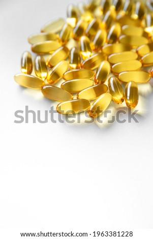 Oliecapsules (zachte capsules) of voedingssupplementen: visolie, omega-3, omega-6, omega-9, vitamine A, vitamine D3, vitamine E, teunisbloemolie, bernagiezaadolie. Gele zachte capsules op wit, ruimte  Stockfoto ©