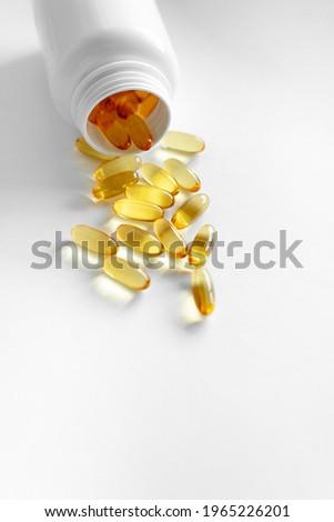 Oliecapsules (zachte capsules) of voedingssupplementen: visolie, omega-3, omega-6, omega-9, vitamine A, vitamine D3, vitamine E, teunisbloemolie, bernagiezaadolie. Gele zachte capsules op een witte ac Stockfoto ©