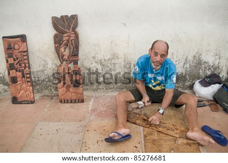 OLINDA, BRAZIL - APRIL 7: Woodcarver works on sidewalk on April 7, 2010 in Olinda, Brazil.  Despite enjoying the strongest economy in South America, 31% of Brazil's 200 million people live below the poverty line.