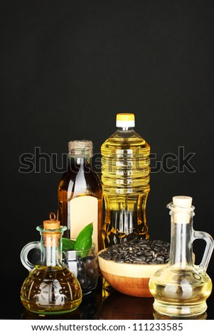 Olive and sunflower oil in the bottles and small decanters isolated on black background close-up