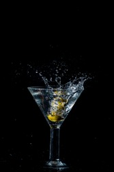 Olive dropped and splashing into a martini on black background