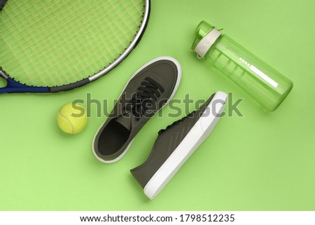 Olive green sneakers with tennis rackets, tennis balls and green plastic water sports bottles on a green background. Minimal photo of sports equipment Foto stock ©