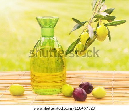 Olive oil and a branch of fresh olives