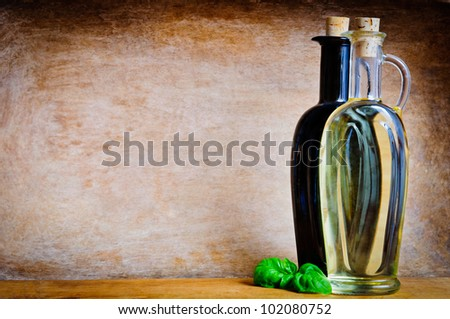 Olive oil and balsamic vinegar with text copy space on a wooden background