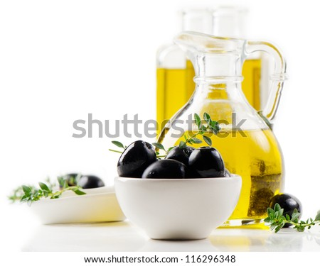 Olive oil and black olives isolated on white