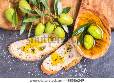Olive oil and fresh branch of olives, bread.Testing fresh mediterranean extra virgin olive oil.