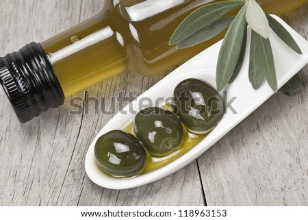 Olive oil bottle and some olives in a china spoon on a wooden surface