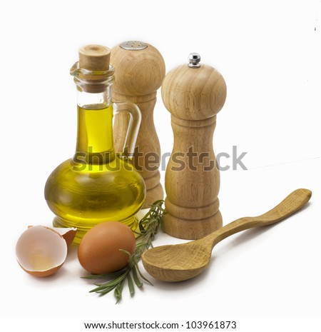 Olive oil, eggs, spices and a wooden spoon on a white background
