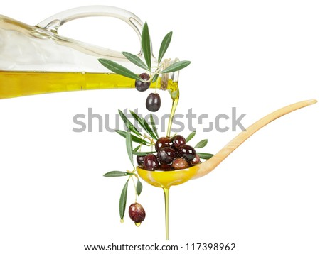 olive oil flows from a bottle in a wooden spoon with branches of an olive tree. Isolated over white background.