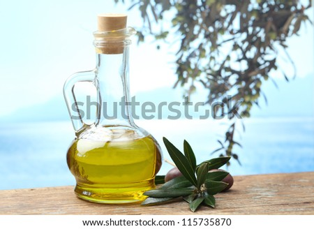 Olive oil in a jug and olive branch with fruits
