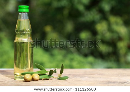 Olive oil in a small bottle on a wooden table with copy space