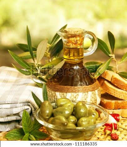 Olive oil in bottle and fresh green olives in glass plate on the table, healthy organic nutrition, traditional Lebanese cuisine, ripe fruits, food still life, Mediterranean vegetables, autumn season