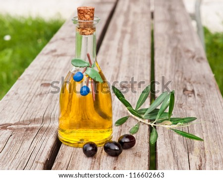 Olive oil in bottle with fresh olives and leaves