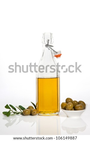 Olive oil in glass bottle, olives in bowl and fresh olive branch and leaves isolated on white background. Culinary cooking.