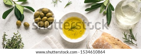 Olive Oil. Organic olive oil  in bowl with green olives, herbs, spices and ciabatta bread on white background , banner, healthy mediterranean food concept. Stock photo ©